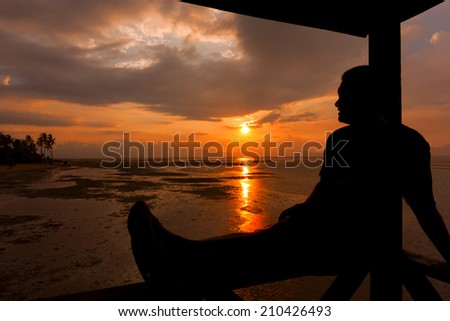 Silhouette of a man relaxing at sunset - stock photo