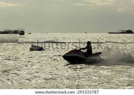 Silhouette of a man ride Jet Ski at Pattaya with banana boat background in summer - stock photo