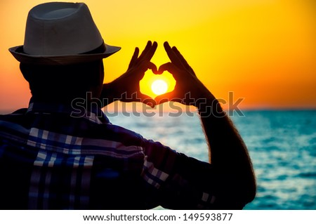 silhouette of a Man showing love  with fingers in the sunset on beach - stock photo