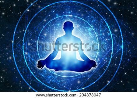 silhouette of a man sitting in a yoga pose of lotus over a space background - stock photo