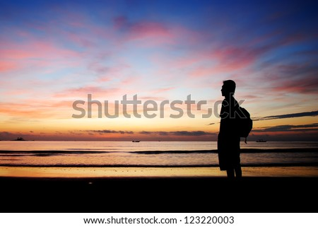 Silhouette of a man standing by the beach in the morning - stock photo