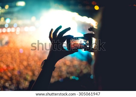 Silhouette of a man using smartphone to take a video at a concert. Modern lifestyle with hipster taking pictures and videos at local concert. Main focus on camera and lights. - stock photo