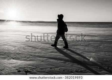 Silhouette of a man walking on a windswept and desolate section of snowy ice on Lake Superior into the sunset. - stock photo