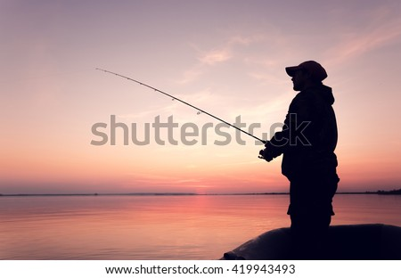 Silhouette of a man with a fishing rod in a boat at sunset - stock photo