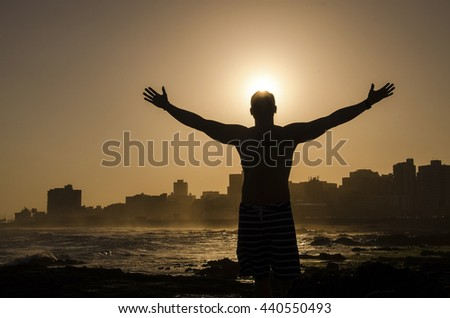 Silhouette of a man with hands raised in the sunset concept for religion, worship, prayer and praise - stock photo