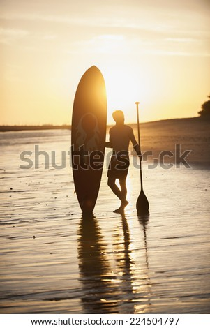 silhouette of a man with his paddle board standing on the beach at sunset - stock photo