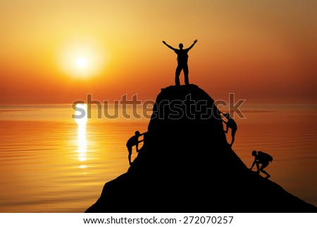 Silhouette of a mans on a mountain top on sunset background. Sport and active life concept  - stock photo