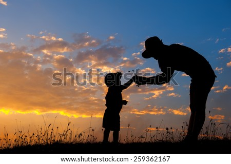 silhouette of a mother and son playing outdoors at sunset - stock photo