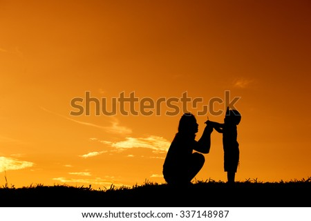 silhouette of a mother and son playing outdoors at sunset with copy space - stock photo