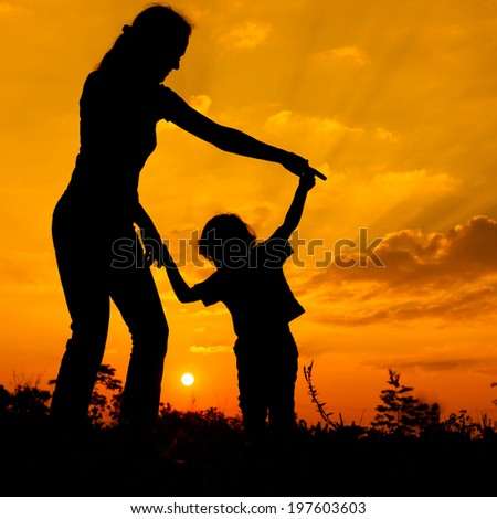 silhouette of a mother and son who play outdoors at sunset background - stock photo