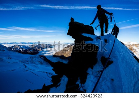 Silhouette of a mountaineer during morning ascent - stock photo