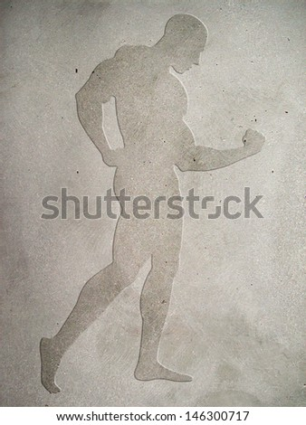 Silhouette of a muscular male figure embossed on concrete wall - stock photo