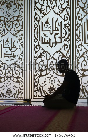 Silhouette of a Muslim praying inside mosque               - stock photo