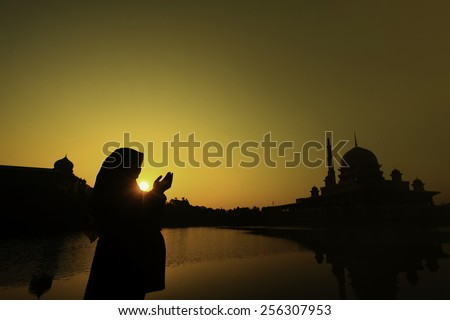 silhouette of a muslim woman praying on the mosque - stock photo