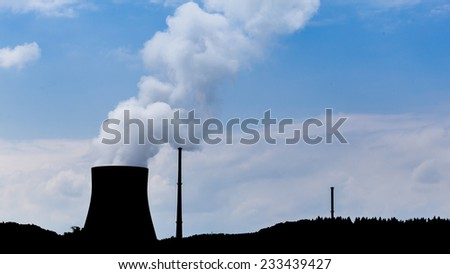 Silhouette of a nuclear power plant cooling tower - stock photo