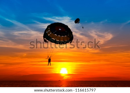 Silhouette of a para-sailor at sunset - stock photo