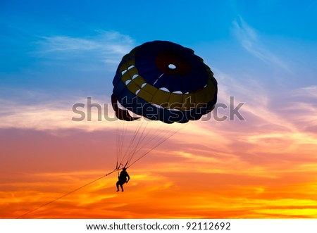Silhouette of a parasailor at sunset - stock photo