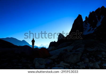 Silhouette of a person looking at the mountains just before sunrise. - stock photo
