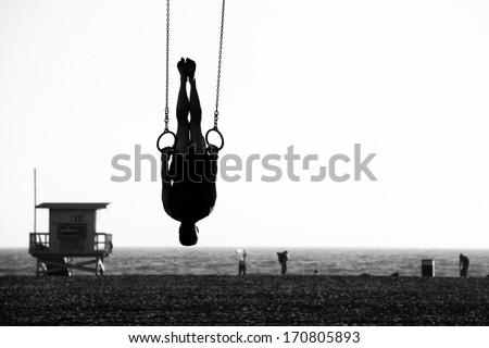 Silhouette of a person swinging on rings on the beach, Santa Monica Beach, Santa Monica, Los Angeles County, California, USA - stock photo