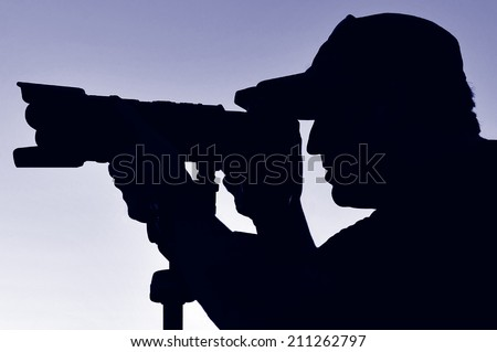Silhouette of a photographer wearing a hat photographing with a camera and tripod nature and wildlife against blue sky. - stock photo