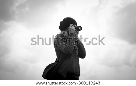 Silhouette of a photographer with cloudy sky. Black and white image