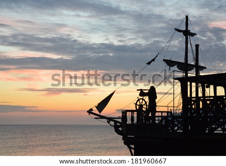 silhouette of a pirate ship with a captain behind steering wheel, looking through spyglass. (not an actual ship, imitation) - stock photo