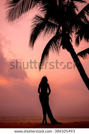 Silhouette of a pretty woman on the tropical beach at sunset - stock photo