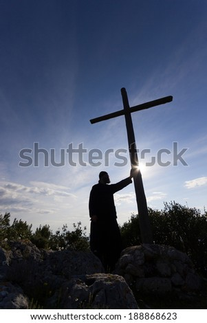 silhouette of a priest holding a cross against the blue sky and the sun  - stock photo