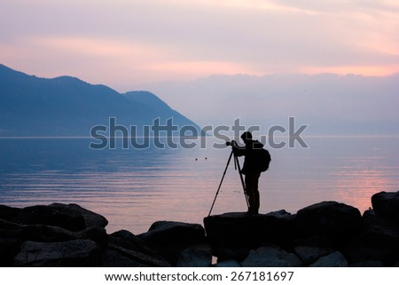 Silhouette of a professional photographer using a tripod, taking a photo of a mountain landscape - stock photo