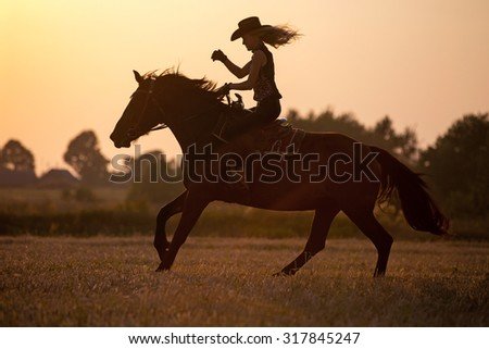 Silhouette of a riding cowgirl. - stock photo