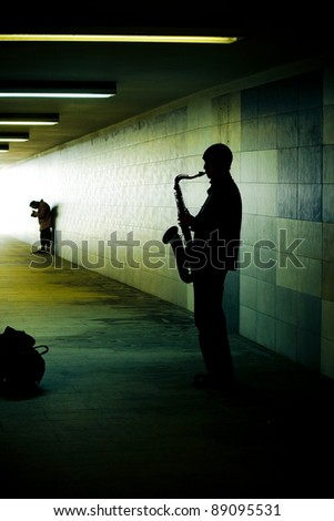 silhouette of a saxophonist in the subway tunnel - stock photo