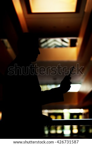 silhouette of a security guard with a portable wireless transceiver in his hand checking the area inside of a blurry building - stock photo