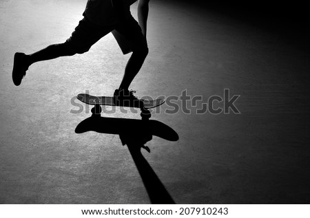 Silhouette of a skateboarder pushing through the skate park.  - stock photo