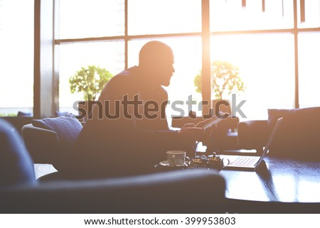 Silhouette of a skilled businessman is working on the idea of expanding his company, while is sitting till late in office with net-book and touch pad. Young male entrepreneur is using digital tablet - stock photo