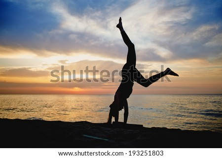 silhouette of a slender woman doing yoga on the sea with a beautiful sunrise - stock photo