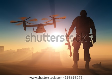 Silhouette of a soldier and a helicopter at sunset. - stock photo