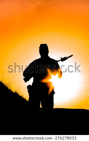 silhouette of a soldier at sunset - stock photo