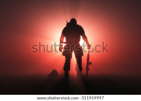 Silhouette of a soldier on a red background. - stock photo
