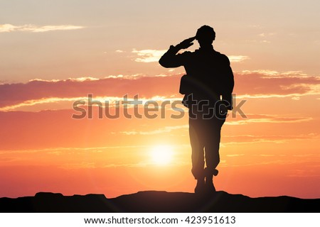 Silhouette Of A Soldier Saluting During Sunset - stock photo