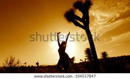 Silhouette of a soulful woman in the desert. - stock photo