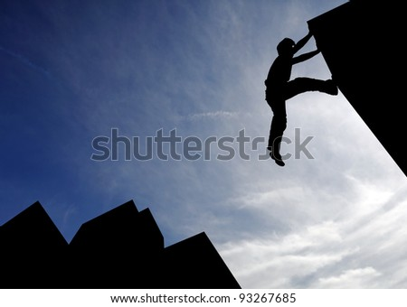 Silhouette of a sport boy scaling a wall in an urban surrounding against a blue cloudy sky for the concept of urban playground. - stock photo