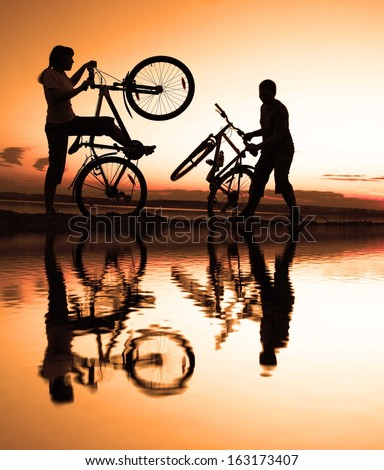 silhouette of a sporty couple in full length at yellow cloudy sunset sky With reflection on water - stock photo