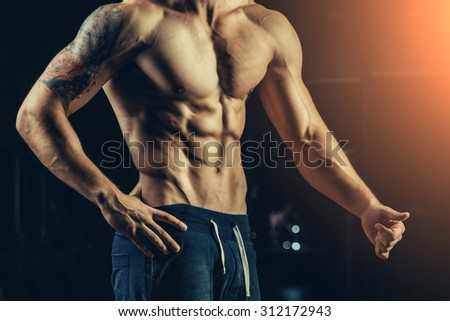 Silhouette of a strong athlete. Confident young fitness man with strong hands. Dramatic light - stock photo