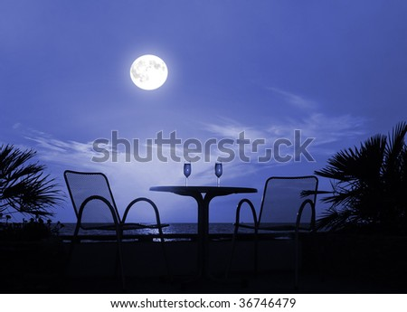 Silhouette of a table with wine glasses on a moon night - stock photo