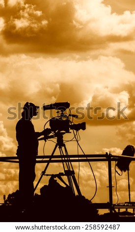 Silhouette of a TV cameraman against a cloudy sky. Post processed to look as during sunset. - stock photo