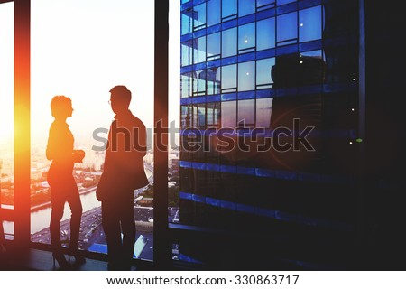 Silhouette of a two successful managing directors discuss ideas after meeting with partners while standing near big office window, young man and woman skilled economists relaxing after conference - stock photo