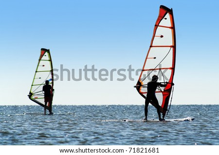 Silhouette of a two windsurfers on the sea surface - stock photo