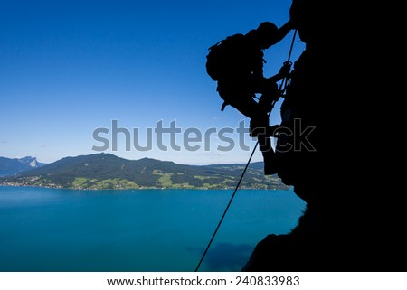 Silhouette of a via ferrata climber high above the lake in Austria - stock photo