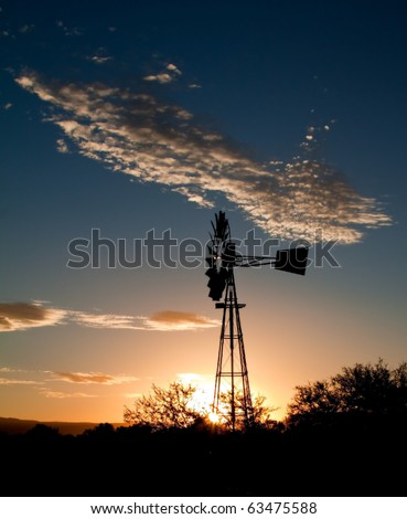 Silhouette of a Windmill at sunset in the Karoo - stock photo