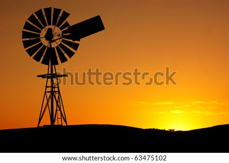 Silhouette of a windmill on a rural farm - stock photo